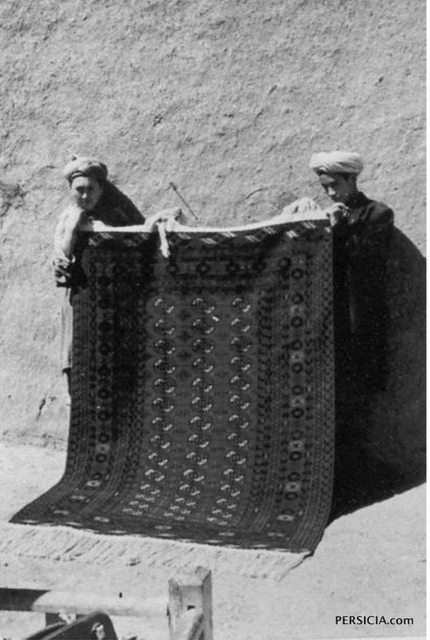 Афганские мальчики демонстрируют традиционный ковер в туркменском стиле европейскому клиенту.